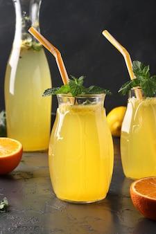 Hausgemachte limonade aus zitronen und orangen, dekoriert mit minze in hohen gläsern mit strohhalmen und einer flasche in der oberfläche, vertikales format, nahaufnahme