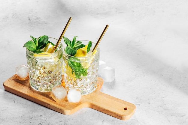 Hausgemachte limonade in eleganten gläsern mit eis auf holzbrett auf weißem marmorhintergrund