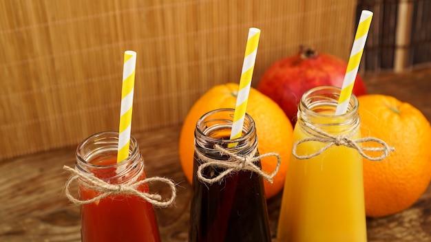 Hausgemachte limonade in kleinen flaschen. bunte säfte und früchte auf holzuntergrund