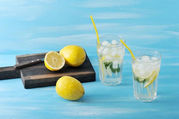 Hausgemachte limonade zitrone, minze, eis und wasser in gläsern