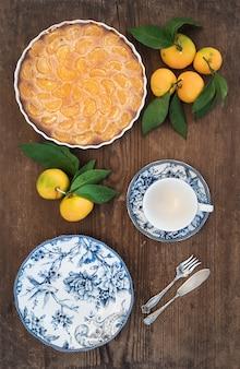 Hausgemachte mandarinen-torte, frisches obst und porzellan-geschirr über rustikalem holz