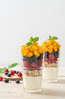 Hausgemachte mango, himbeere und blaubeere mit joghurt und müsli - gesunde ernährung