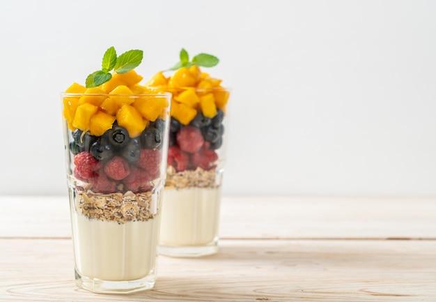 Hausgemachte mango, himbeere und heidelbeere mit joghurt und müsli - gesunder food-style