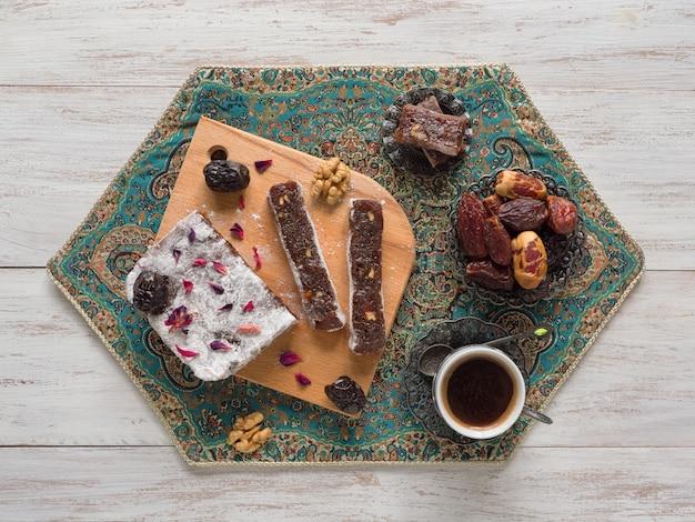 Hausgemachte marmeladenbonbons mit dattelfrüchten und nüssen, östliche bonbons auf einer weißen holzoberfläche.