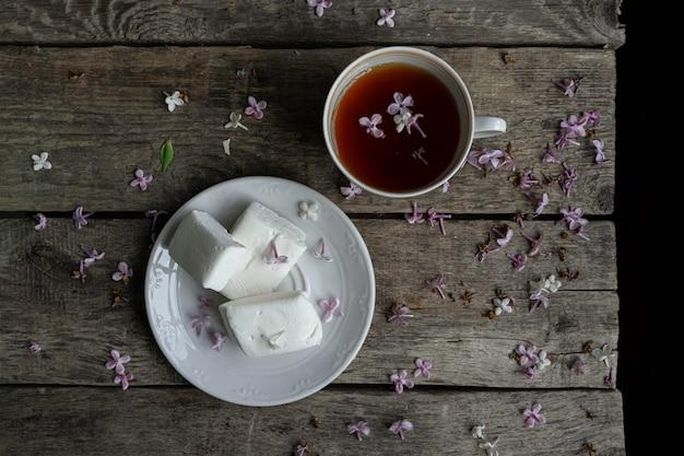 Hausgemachte marshmallows, tee, lila blütenblätter auf altem holztisch