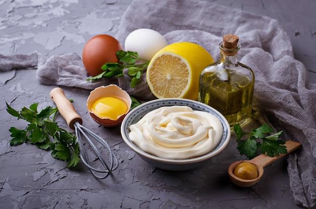 Hausgemachte mayonnaise-sauce und olivenöl, eier, senf, zitrone. selektiver fokus