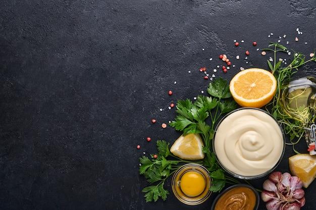 Hausgemachte mayonnaise-sauce und zutaten zitrone, eier, olivenöl, gewürze und kräuter, schwarzer hintergrundkopierraum. essen kochen hintergrund. ansicht von oben.