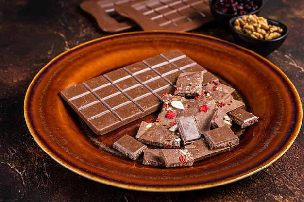 Hausgemachte milchschokolade mit haselnüssen, erdnüssen, preiselbeeren und gefriergetrockneten himbeeren auf einem rustikalen teller. dunkler hintergrund. ansicht von oben.