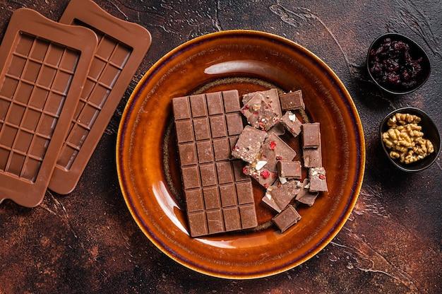 Hausgemachte milchschokolade mit haselnüssen, erdnüssen, preiselbeeren und gefriergetrockneten himbeeren auf einem rustikalen teller. dunkler hintergrund. draufsicht.