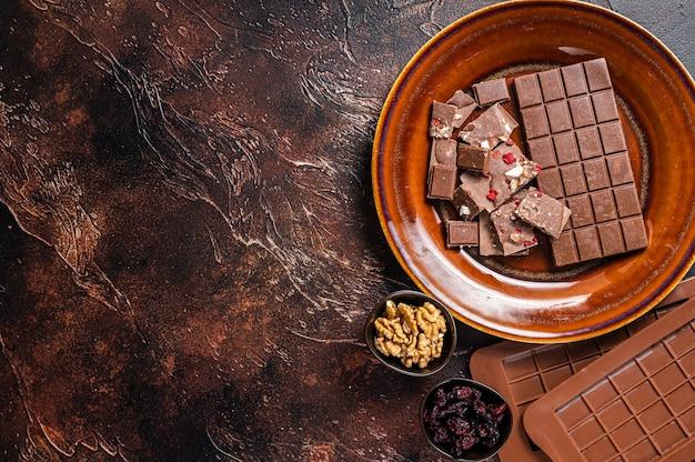 Hausgemachte milchschokolade mit haselnüssen, erdnüssen, preiselbeeren und gefriergetrockneten himbeeren auf einem rustikalen teller