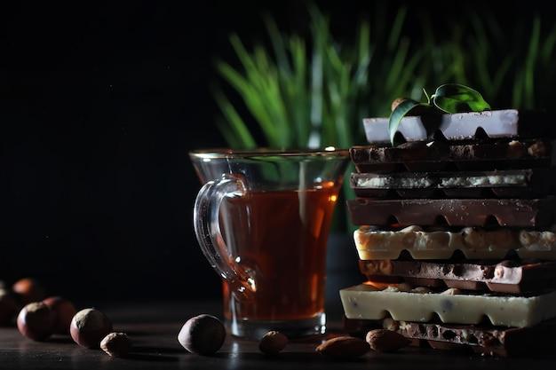 Hausgemachte milchschokolade mit mandeln und getrockneten erdbeeren. stücke von milchschokolade. satz milchschokolade mit tee.