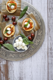 Hausgemachte mini-pizza margarita mit tomaten, mozzarella und basilikum