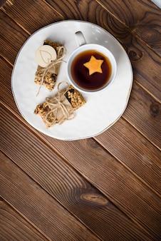 Hausgemachte müsli haferflocken energieriegel und tasse tee auf weißem teller, gesunder snack, kopierraum auf holz schreibtisch