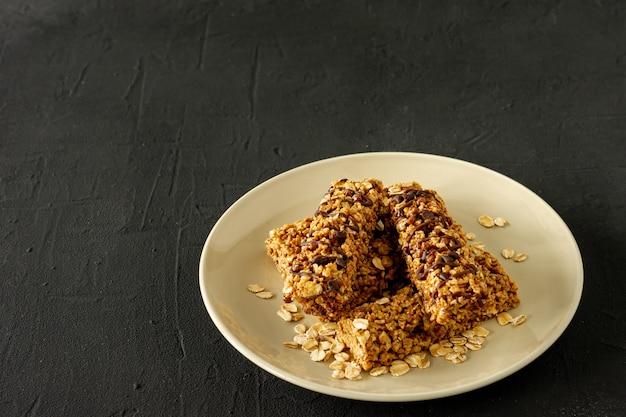 Hausgemachte müsliriegel mit mandeln und rosinen auf schwarzem gesundes essen.