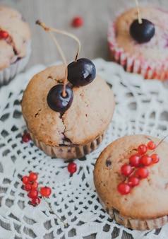 Hausgemachte muffins gefüllt mit kirschen und roter johannisbeere