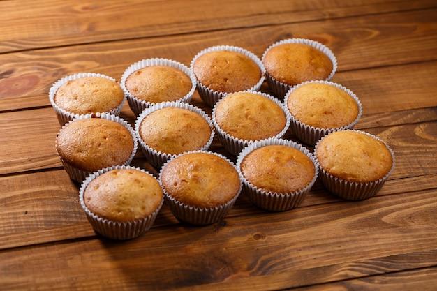 Hausgemachte muffins im papierwickel auf holzbrett