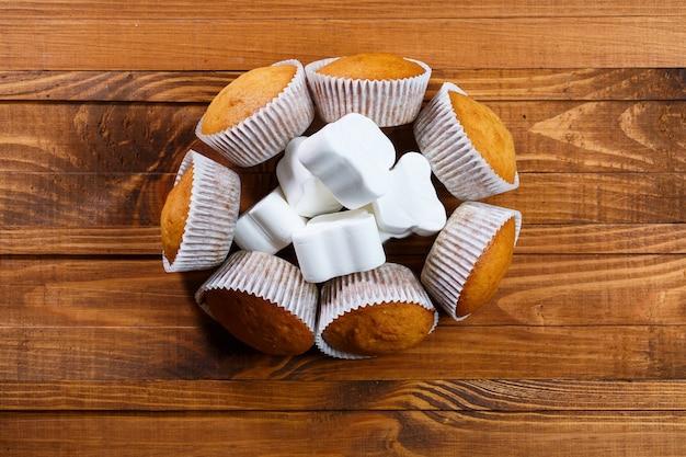 Hausgemachte muffins im papierwickel mit marshmallows auf holzbrett
