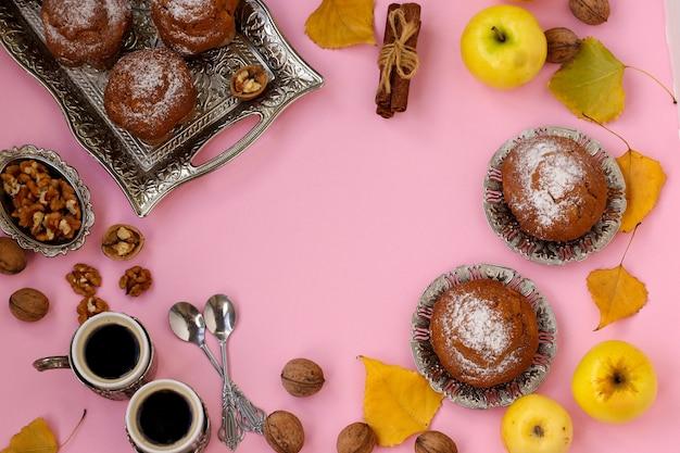 Hausgemachte muffins mit äpfeln und nüssen und zwei tassen kaffee angeordnet auf einem rosa hintergrund, draufsicht, kopierraum, herbstkomposition, horizontale ausrichtung
