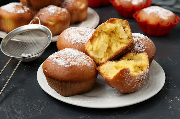 Hausgemachte muffins mit ananasstücken, bestreut mit puderzucker