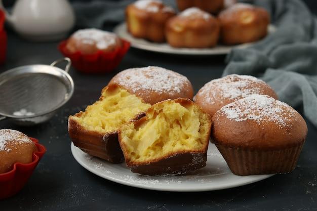 Hausgemachte muffins mit ananasstücken, mit puderzucker bestreut, im dunkeln angeordnet.