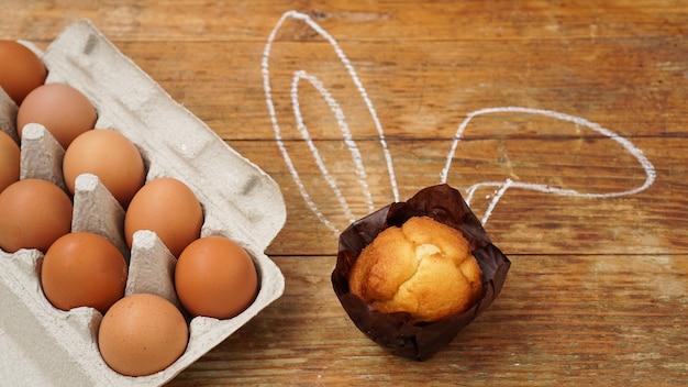 Hausgemachte muffins mit bemalten hasenohren. muffins und eier auf einer holzoberfläche.