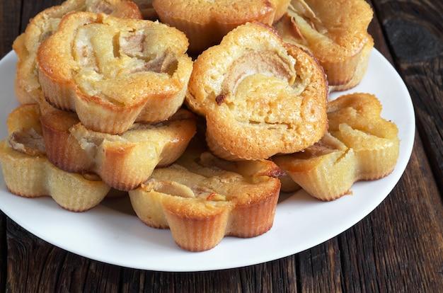 Hausgemachte muffins mit birnen im teller auf dunklem holztisch schließen oben
