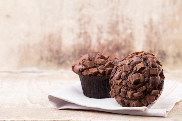 Hausgemachte muffins mit schokolade, weinlesehintergrund.