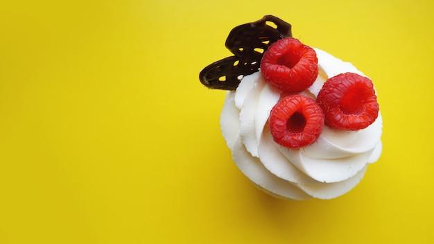 Hausgemachte muffins mit süßer sahne und frischen roten himbeeren auf einer gelben oberfläche schließen. draufsicht