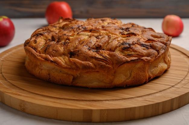 Hausgemachte nahaufnahme gesunder traditioneller kornischer apfelkuchen auf einem weißen tisch. neben drei äpfeln. ansicht von oben. horizontale ausrichtung