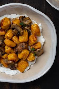 Hausgemachte nudel-kürbis-gnocchi mit pilzsauce und ricotta auf dunklem holztisch