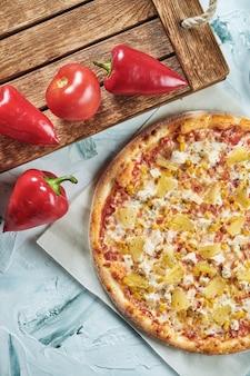 Hausgemachte ofengebackene hawaiianische pizza mit hühnchen und ananas, rote sauce. zusammensetzung mit knuspriger pizza, tomaten.