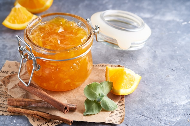 Hausgemachte orangenmarmelade im glas auf einem grauen tisch. lebensmittelhintergrund