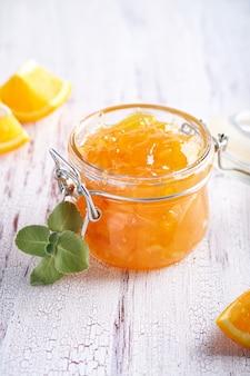 Hausgemachte orangenmarmelade im glas auf einem weißen tisch. lebensmittelhintergrund