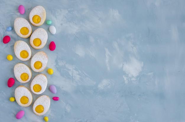 Hausgemachte osterplätzchen in form von osterei mit puderzucker und zitronencreme auf hellblauem betonhintergrund. grußkarte. osterhintergrund.