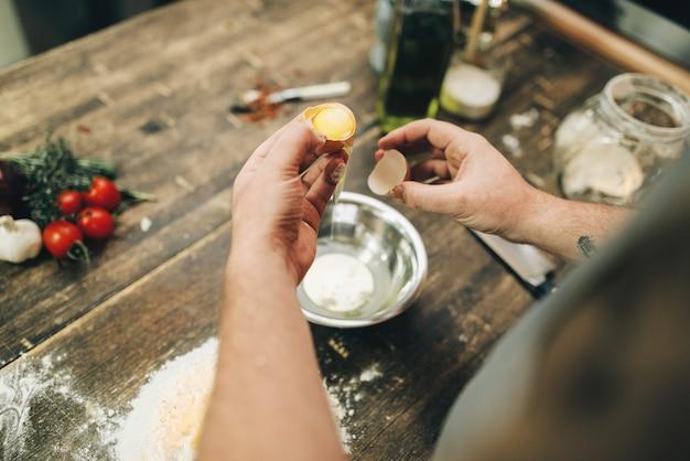 Hausgemachte pasta kochprozess, teigzubereitung. männliche kochhände mit ei, ein bündel mehl auf holztisch