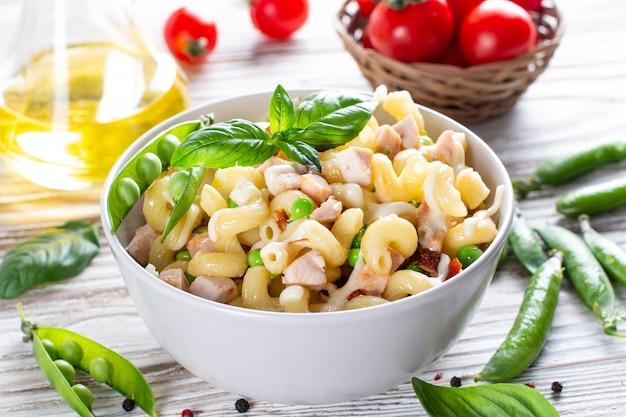 Hausgemachte pasta mit grünen erbsen, hühnchen und sahnesauce auf hellem holzhintergrund. salat mit hühnchen und grünen erbsen
