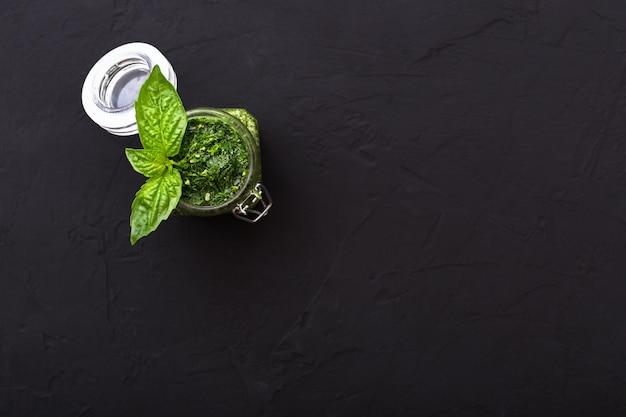Hausgemachte pestosauce und grüner basilikum auf dunklem zementhintergrund. italienische grüne pesto-sauce im glas für pasta, spaghetti. vegetarisches gesundes essen. ansicht von oben, flach mit kopienraum für text.