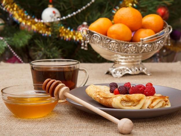 Hausgemachte pfannkuchen auf teller, tasse tee und honig in glasschüssel mit holzlöffel, metallvase mit orangen auf sackleinen. tannenbaum mit spielzeugbällen und girlande im hintergrund. heiligabend-konzept.