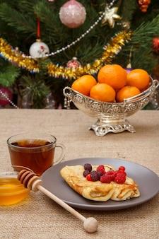 Hausgemachte pfannkuchen auf teller, tasse tee und honig in glasschüssel mit holzlöffel, metallvase mit orangen auf sackleinen. tannenbaum mit spielzeugbällen und girlande im hintergrund.