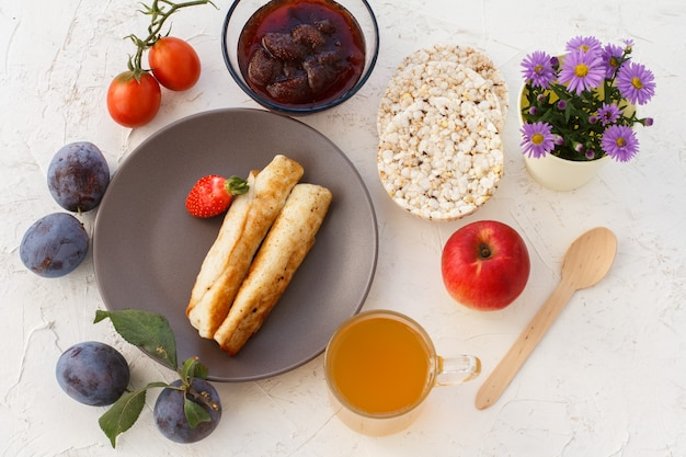 Hausgemachte pfannkuchen gefüllt mit hüttenkäse, eine erdbeere auf dem teller, pflaumen, eine glasschüssel mit marmelade, ein holzlöffel, äpfel, puffreiskuchen, eine tasse tee und blumen. ansicht von oben.