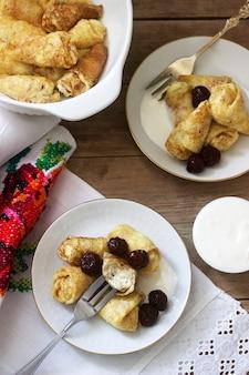 Hausgemachte pfannkuchen gefüllt mit hüttenkäse mit rosinen, serviert mit saurer sahne und kirsche.