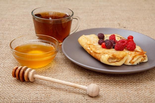 Hausgemachte pfannkuchen gefüllt mit hüttenkäse und belegt mit gefrorenen himbeeren und brombeeren auf teller, tasse tee und honig in glasschüssel mit holzlöffel auf sackleinen
