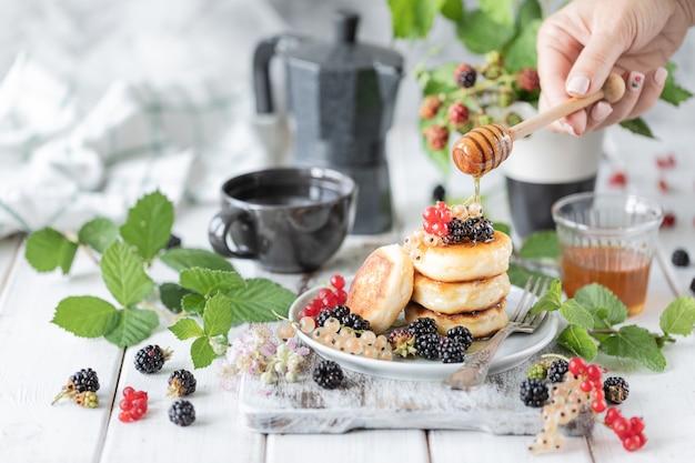 Hausgemachte pfannkuchen mit beeren und wecker auf weißem holz