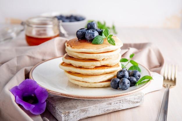 Hausgemachte pfannkuchen mit blaubeeren und puderzucker auf dem weißen tisch.