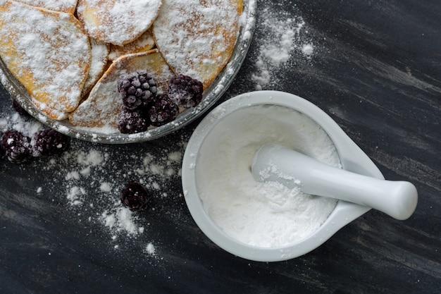 Hausgemachte pfannkuchen mit brombeeren, puderzucker