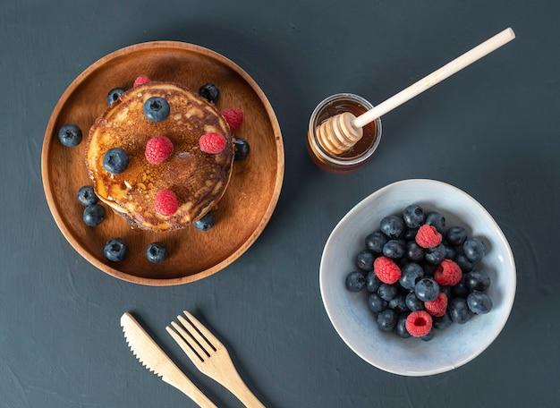 Hausgemachte pfannkuchen mit frischen blaubeeren, himbeeren und honig. draufsicht