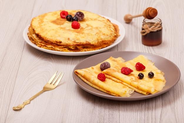 Hausgemachte pfannkuchen mit gefrorenen himbeeren und brombeeren auf tellern und honig in glasschüssel mit holzlöffel auf holzhintergrund.