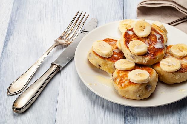 Hausgemachte pfannkuchen mit rosinen, die mit kondensmilch übergossen und mit geschnittenen bananen serviert werden