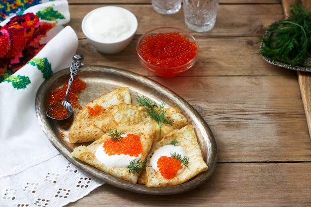 Hausgemachte pfannkuchen mit rotem kaviar, sauerrahm und dill, serviert mit wodka. rustikaler stil.
