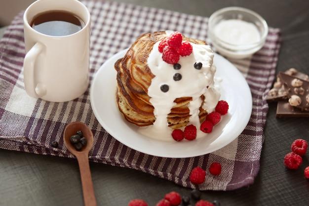 Hausgemachte pfannkuchen mit saurer sahne auf weißem teller mit beeren, frischen blaubeeren und himbeeren, tasse tee oder kaffee, löffel, chocholatstücke auf kariertem baumwolltuch.